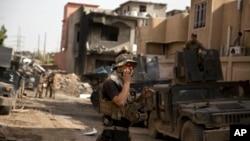 Боец иракского спецназа говорит по рации со связистом подразделения, выбивающего боевиков ИГИЛ из другого района Мосула. 12 апреля 2017 г.