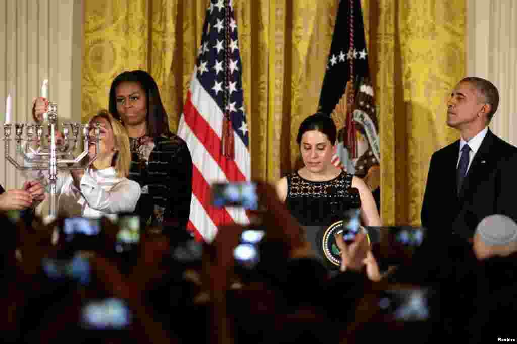 باراک اوباما، رئیس جمهوری آمریکا و میشل اوباما، همسر او، در مراسم روشن کردن شمعدان هفت شاخه نشان مذهب یهودیان در کاخ سفید.