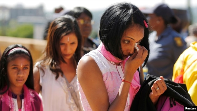 A woman weeps after paying her respects to Nelson Mandela as Mandela lies in state  at the Union Buildings in Pretoria, Dec. 12, 2013.