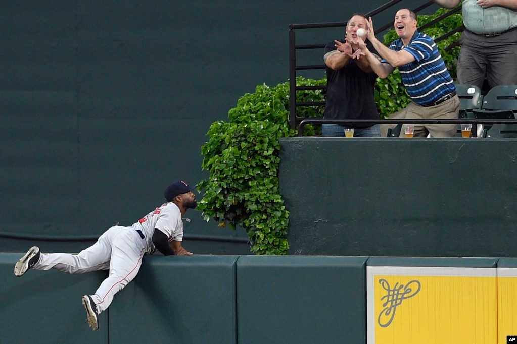 Boston Red Sox center fielder Jackie Bradley Jr., left, watches fans go for a ball hit by Baltimore Orioles & #39; Jonathan Villar for a grand slam during the second inning of a baseball game, May 6, 2019, in Baltimore, Maryland.