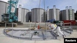 지난 10일 일본 후쿠시마 원자력 발전소에서 보호복을 입은 직원들이 오염수 저장 탱크 주변을 점검하고 있다.
