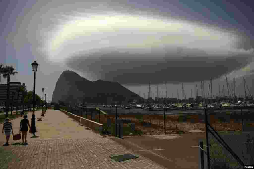 People walk along a street in front of the Rock of the British territory of Gibraltar (rear), a monolithic limestone promontory, next to the border in La Linea de la Concepcion, southern Spain.