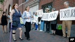 Boston Marathon bombing victim Erika Brannock, foreground left, and her mother, Carol Downing, foreground right, walk past demonstrators outside federal court in Boston, June 24, 2015.