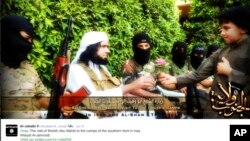 FILE - This screen grab from an Islamic State group affiliated Twitter account, taken Sunday, Sept. 20, 2014, purports to show senior military commander Abu Wahib handing a flower to a child while visiting southern Iraq, as part of the group's broad social media campaign.