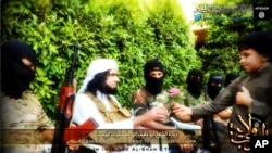 FILE - Screengrab from Islamic State-linked Twitter account purports to show senior military commander Abu Wahib handing a flower to a child while visiting southern Iraq, Sept. 20, 2014.