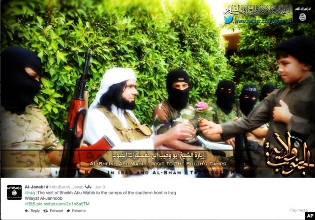 FILE - This screen grab from an Islamic State group-affiliated Twitter account, taken Sept. 20, 2014, purports to show a military commander handing a flower to a child while visiting southern Iraq. The group is a leader in using Internet-based communications.