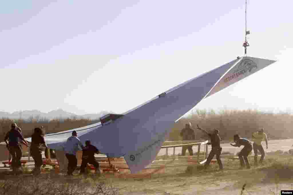 Trabajadores del Museo del Aire y el Espacio de Pima preparan el lanzamiento del avión de papel de casi 14 metros de largo.