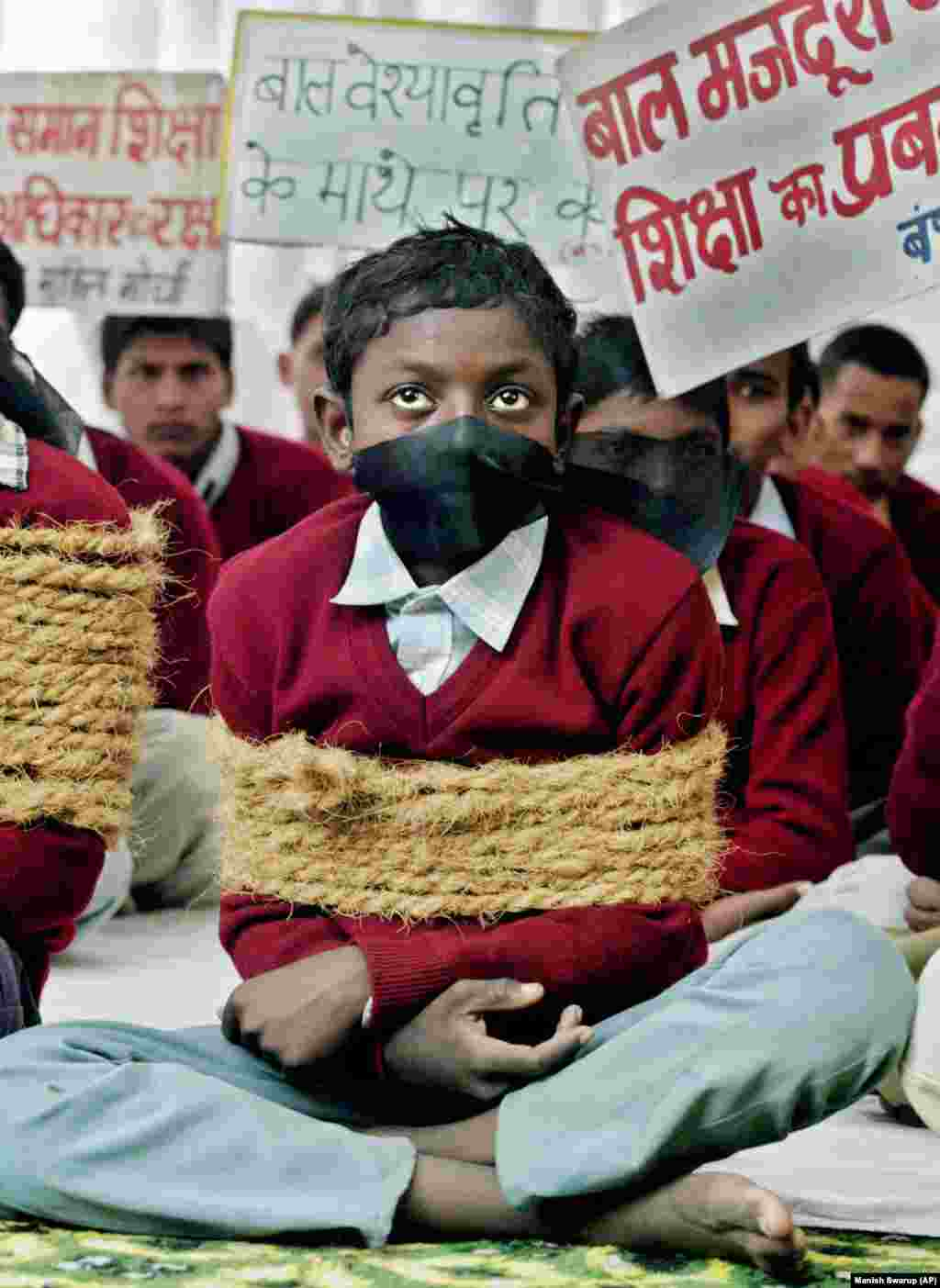 Índia: Crianças simulam estarem presas, em protesto contra o trabalho infantil e forçado no país.