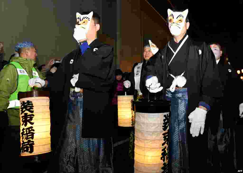 Residents in fox masks participate in the Oji Fox parade to thank the outgoing and welcome the incoming year at the Oji Inari shrine in Tokyo, Japan, Jan. 1, 2018.