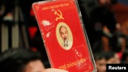 A delegate of Vietnam's Communist Party raises his membership card to vote on new policies at the closing ceremony of the 11th National Congress of the Party in Hanoi January 19, 2011