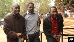 Zimbabwean journalists Brian Chitemba, left, Mabasa Sasa, center, and Tinashe Farawo walk in handcuffs, outside the magistrates courts in Harare, Zimbabwe, Nov. 4.2015.