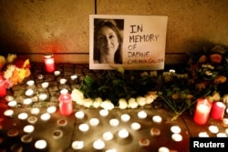 Candles burn to commemorate the killed investigative journalist Daphne Caruana Galizia in Berlin, Germany, Oct. 20, 2017.