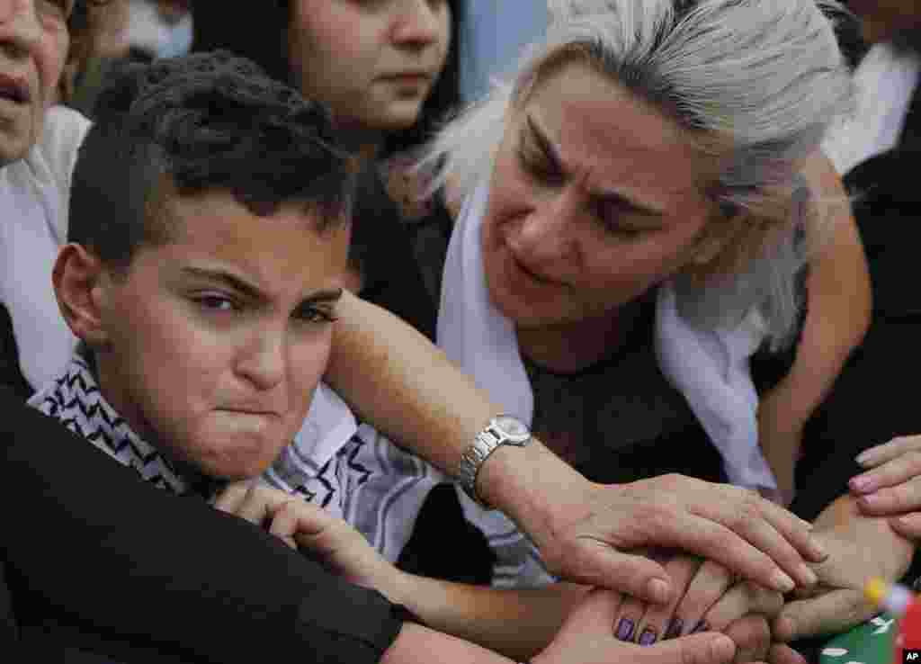 Omar, left, and his mother Lara, attend the Beirut funeral of their father and husband, Alaa Abu Fakher, who was killed by a Lebanese soldier during protests Tuesday night south of the capital.
