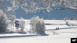 Deux randonneurs empruntent une route enneigée à Lofer, province autrichienne de Salzbourg, le 18 janvier 2016.