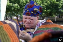 FILE - Tanzanian Albino, Muadhani Ramadhani, weaves an Africa tradition carpet (Mat) at Mnazi Mmoja grounds in Dares Salaam, May 4, 2007, as part of celebrations to mark World Albino Day. They appealed to the government and public at large that they disse