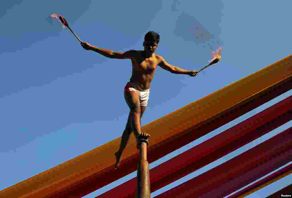 "A man performs ""Malkhamb"" (traditional Indian gymnastics) during a college festival in Mumbai, India."