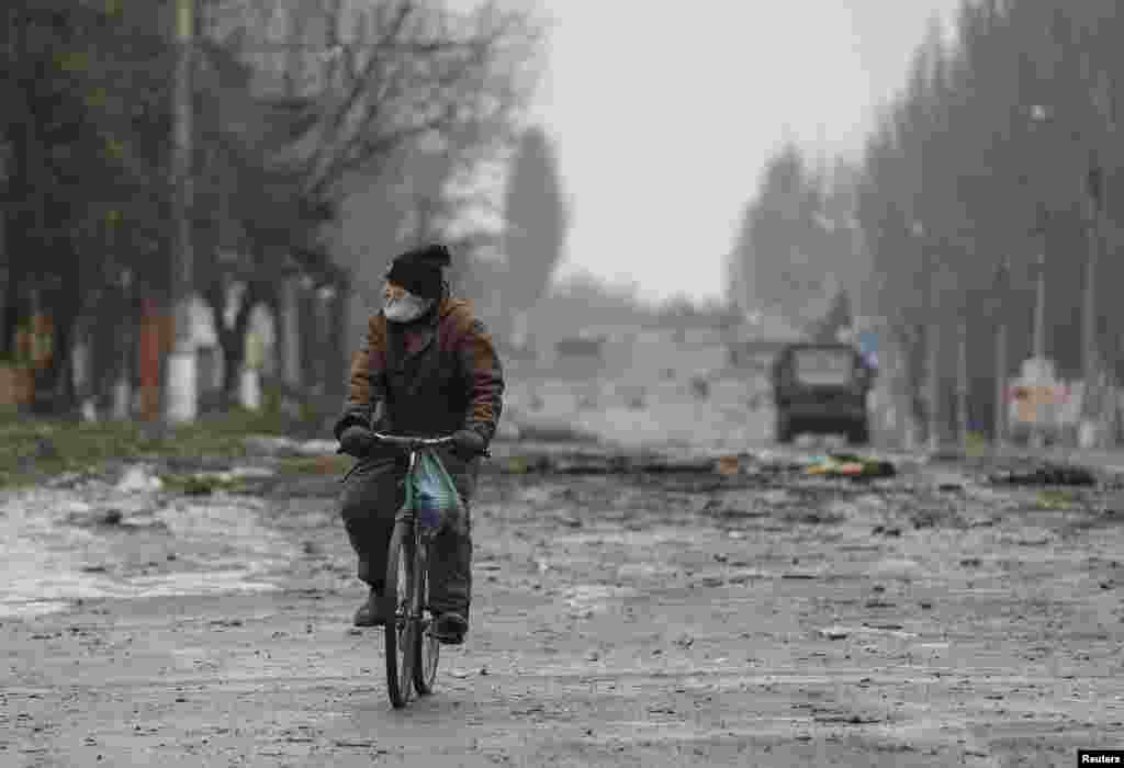 A local resident rides his bicycle along a street in Vuhlehirsk, Donetsk region, Feb. 6, 2015.