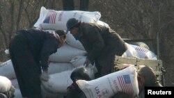 지난 2008년 12월 북한 신의주 주민들이 미국에서 지원한 식량을 트럭에서 내리고 있다. 식량 자루에 'USAID(미국제개발처)' '미국에서 보내온 선물' 이란 문구가 씌여있다. (자료사진)