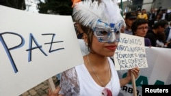 "FILE - A demonstrator holds a sign reading ""Peace"" during a march in Bogota, Nov. 19, 2014."