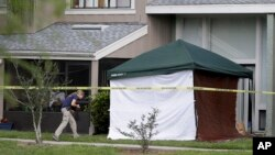 An FBI investigator walks to the apartment where a man was shot by an FBI agent, Wednesday, May 22, 2013, in Orlando, Fla.