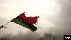 LIbijska zastava i u pozadini dim izazvan bombaškim napadom.