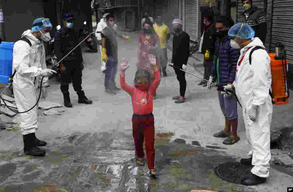 A young Nepalese girl is sprayed with disinfectants as she arrives to get free food distributed by social workers during a lockdown to control the spread of the new coronavirus in Kathmandu.