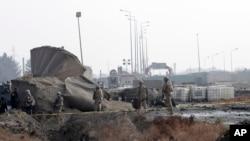 Pasukan AS memerikasa lokasi pasca serangan bom bunuh diri dekat gerbang NATO di Kabul, Afghanistan (11/12).