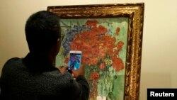 "Seorang pria mengabadikan lukisan Vincent van Gogh, ""Vase with Daisies and Poppies"", di balai lelang Sotheby di Hong Kong, 6 Desember 2014. (Foto: Reuters/Ilustrasi)"