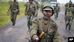 Tentara Kongo berbaris menuju kota Kibumba setelah merebutnya dari pemberontak M23 (28/10). (AP/Joseph Kay)
