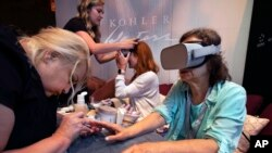 In this Tuesday, Aug. 6, 2019, photo, Kohler Waters Spa cosmetologist Jodi Gerk, left, performs a virtual reality manicure at the 2019 International Spa Association event, in New York. (AP Photo/Richard Drew)