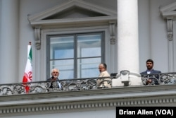 Iranian Foreign Minister Mohammad Javad Zarif, left, stands on the balcony of Palais Coburg, the venue for nuclear talks, in Vienna, Austria, July 2, 2015.