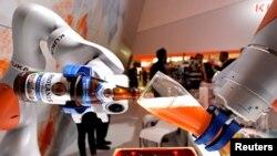 """已被中国美的公司收购的德国机器人巨头""""库卡""""公司在汉诺威举行的工业展销会上展示机器人手臂倒一杯德国啤酒。(2017年4月24日)"""