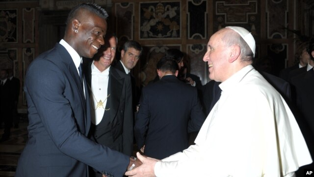 In this photo provided by the Vatican newspaper L'Osservatore Romano, Pope Francis greets Italy forward Mario Balotelli during a private audience at the Vatican, Aug. 13, 2013.
