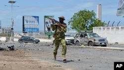FILE - An armed Somali soldier runs to fight during an attack on Somalia's parliament in Mogadishu, May 24, 2014.