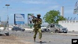 Seorang tentara Somalia berlari di tengah serangan terhadap parlemen Somalia di Mogadishu, Mei 2014.