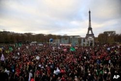Activists gather near the Eiffel Tower during the COP21, the United Nations Climate Change Conference, in Paris, Dec.12, 2015.
