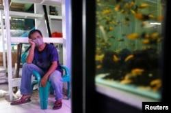 Seorang pedagang ikan hias menunggu pembeli di sebuah pasar di tengah pandemi virus corona (Covid-19) di Jakarta, 13 Mei 2020. (Foto: Reuters)