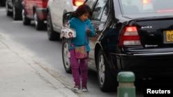 Une petite fille vend des bonbons dans une rue du quartier de Miraflores à Lima, au Pérou, le 8 août 2014.