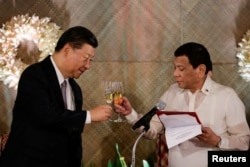 FILE - China's President Xi Jinping and Philippine President Rodrigo Duterte toast during a State Banquet at the Malacanang presidential palace in Manila, Philippines, Nov. 20, 2018.