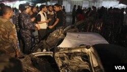 Warga Palestina berkumpul di dekat mobil yang terkena serangan udara Israel di Gaza.