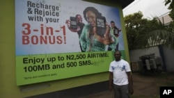A man walk past a giant advertisement bill board of Nigeria Globacom in Lagos, Nigeria, May, 13. 2012.