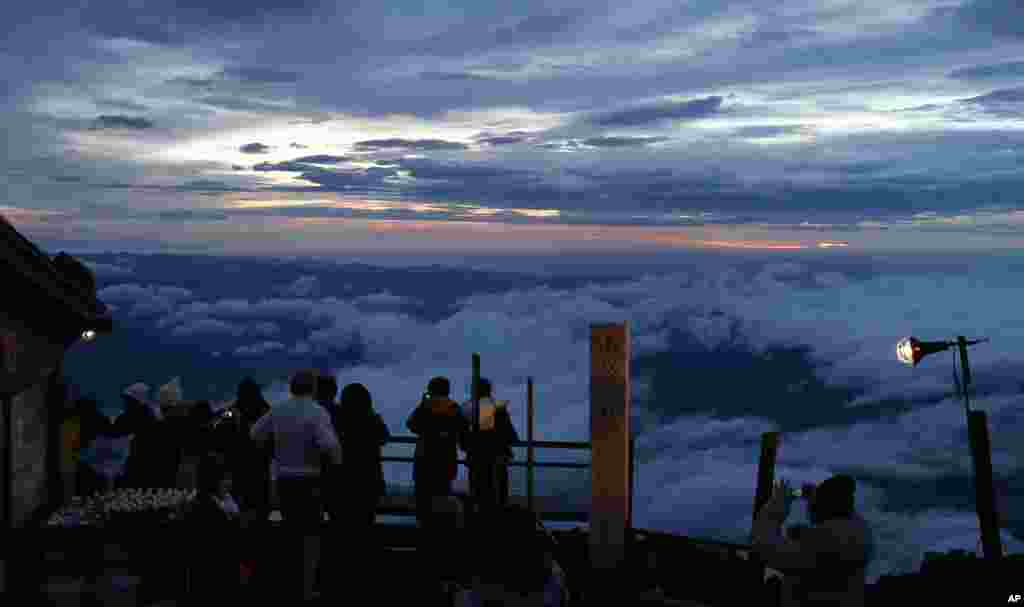 Climbers view the sunrise in early morning on Mount Fuji in Fujiyoshida city, Yamanashi prefecture, Japan.