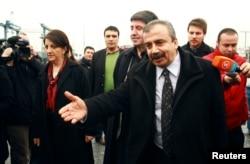 FILE - Pro-Kurdish politicians Sirri Sureyya Onder (R), Pelvin Buldan (L) and Altan Tan (C), are surrounded by media members before leaving for Imrali island in Istanbul, Feb. 23, 2013.