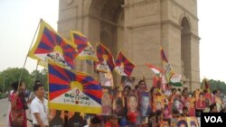 Exile tibetans hod photos of those who self immolated for the cause of tibet during a candle light vigil near the india gate monute, in background, in New Dehi, India, Wedneday, July 25, 2012