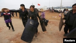 Villagers carry police shields taken from police injured during clashes at Fuyou village in Jinning county, Kunming, Yunnan province, Oct. 15, 2014.