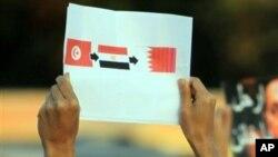 ຜູ້ຊາຍຊາວ Bahrain ຍົກເຈ້ຍທີ່ມີຮູບທຸງຊາດ ທີ່ມີຄວາມໝາຍວ່າ ປະເທດຂອງລາວ ຈະເປັນປະເທດຕໍ່ໄປ ໃນການປ່ຽນແປງທາງ ການເມືອງ ໄປສູ່ປະຊາທິປະໄຕ.