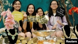 """Attendees at a booth promoting the new movie """"Crazy Rich Asians"""" as they participate at KCON USA, billed as the world's largest Korean culture convention and music festival, in Los Angeles, California, Aug. 10, 2018."""
