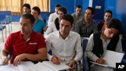 FILE - Afghan students take notes in a business administration class at Kardan University in Kabul, Afghanistan, Sept. 10, 2013. By targeting the educated militants hope to increase the number of uneducated youth – a prime demographic in Afghanistan.