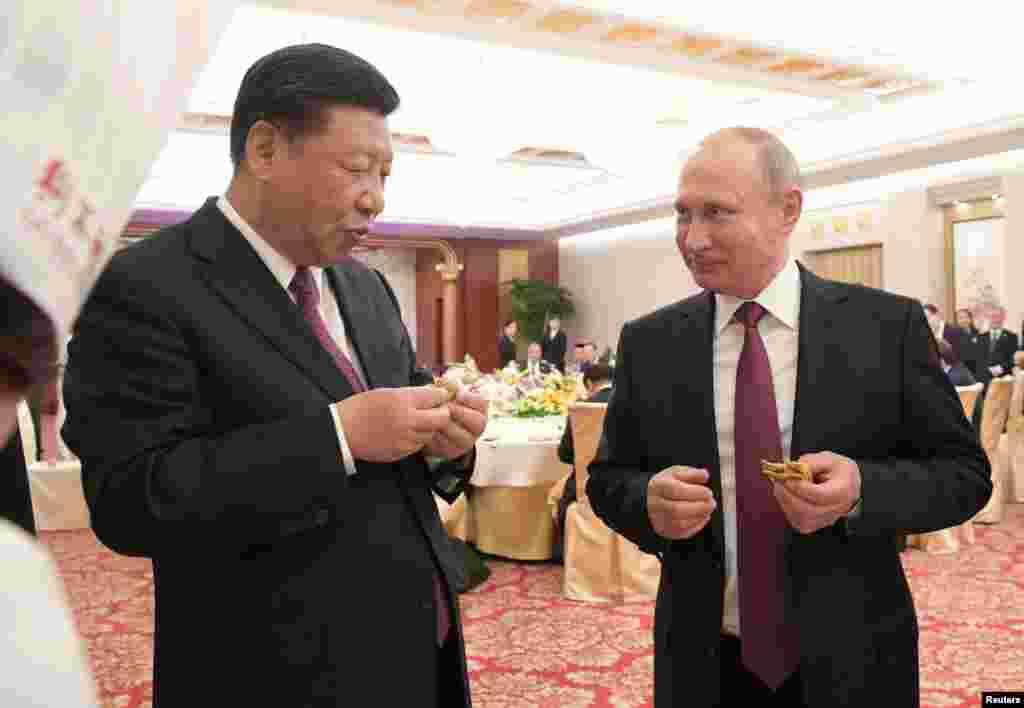 """俄罗斯总统普京和中国国家主席习近平2018年6月8日在中国天津出席招待会,吃煎饼果子。当天习近平授予普京""""友谊勋章""""。习近平强调,这枚勋章不仅代表了中国人对普京的崇高敬意,更象征了两个国家的深厚友谊。 习近平还说:""""中华人民共和国'友谊勋章'是中国国家对外最高荣誉勋章。"""" 2017年7月4日,普京授予习近平俄罗斯国家最高勋章""""圣安德烈""""勋章。"""