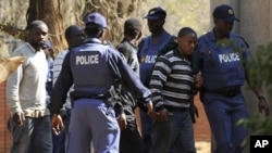Police keep watch during the arrival of some of the 250 mine workers who were arrested when they had a shoot out with police, at a Garankuwa court outside Pretoria, South Africa, August 20, 2012.